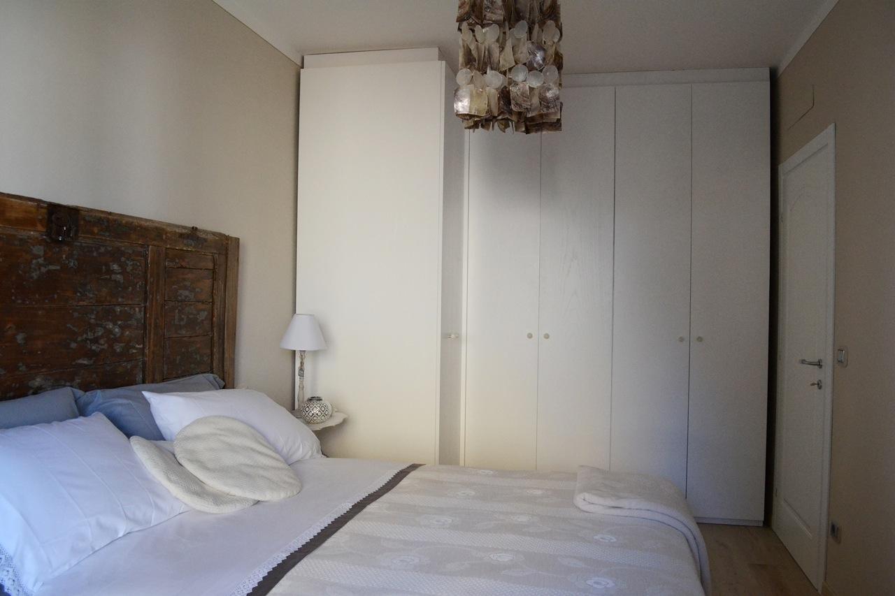 Casa GL - Camera matrimoniale con armadio su misura e testata del letto in legno, abat-jour in tessuto - Tommaso Vecci