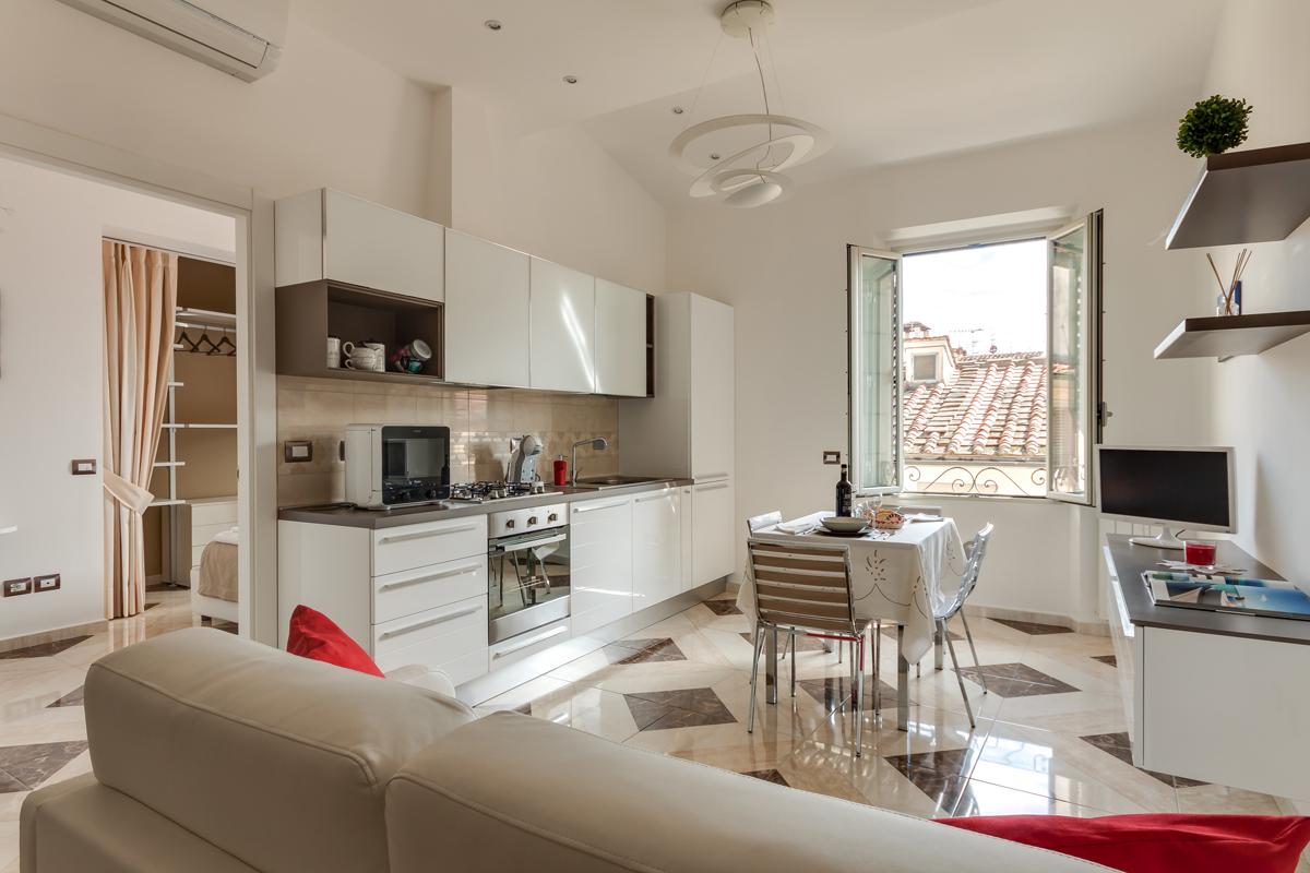 Casa DM1 - Vista del soggiorno con faretti da incasso, angolo cottura e affaccio verso l'esterno - Tommaso Vecci