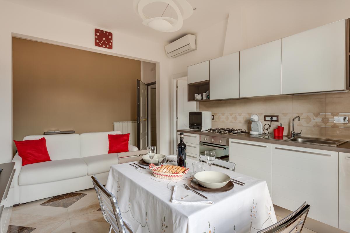 Casa DM1 - Portale di collegamento tra ingresso e soggiorno, divano colori chiari e cuscini colorati - Tommaso Vecci