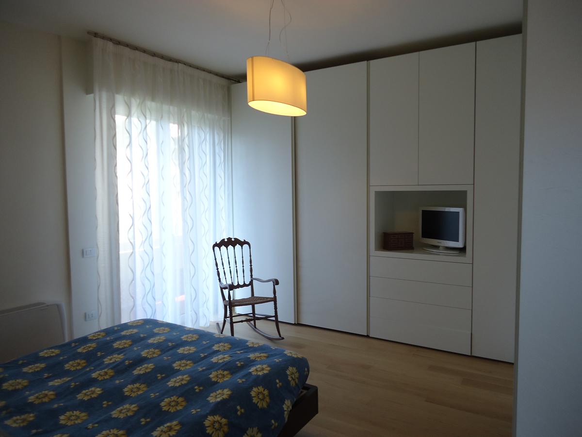 Casa - PG - Camera da letto con sedia a dondolo e lampada con paralume in tessuto cotonette beige - Tommaso Vecci