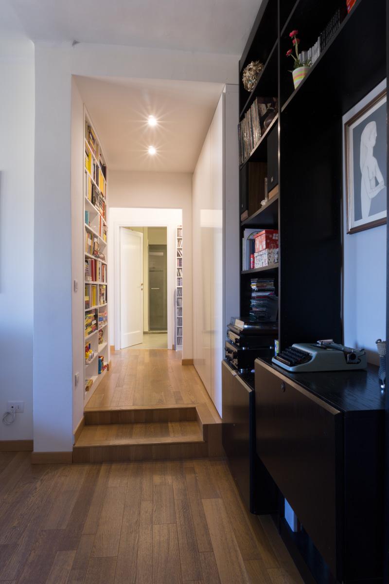 Casa C2- Zona ingresso con libreria a muro, controsoffitto con faretti e pavimento in legno - Tommaso Vecci