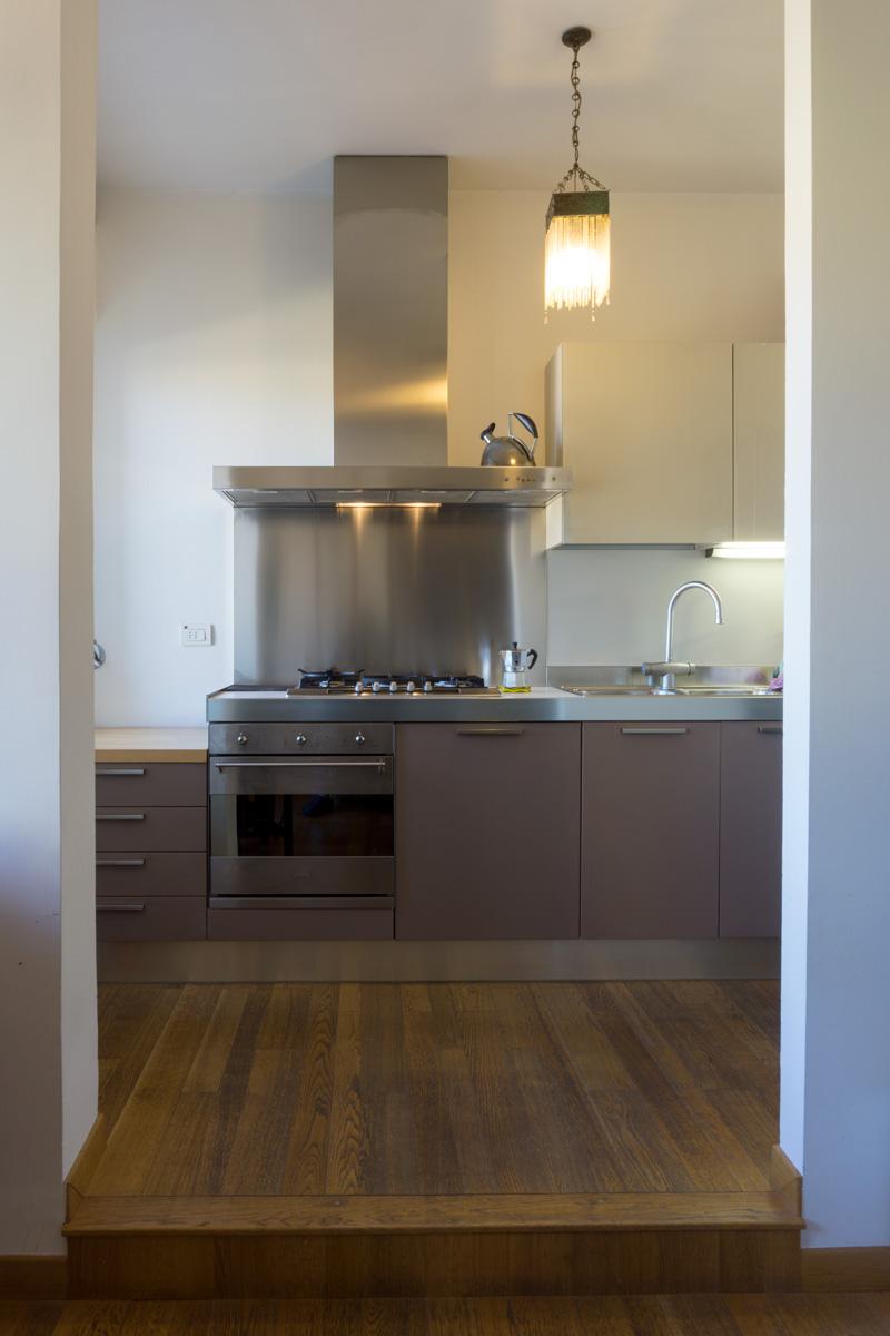 Casa C2- Dettaglio zona cottura, cucina color tortora, maniglie e cappa in acciaio, lampadario decò - Tommaso Vecci