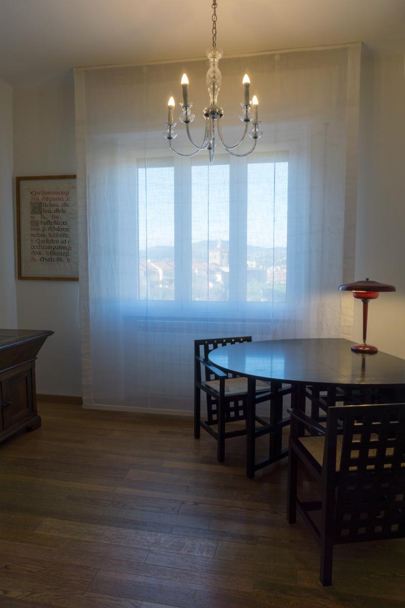 Casa C2- Soggiorno con pavimento in legno, tavolo e sedie in legno di colore nero, lampadario decò - Tommaso Vecci