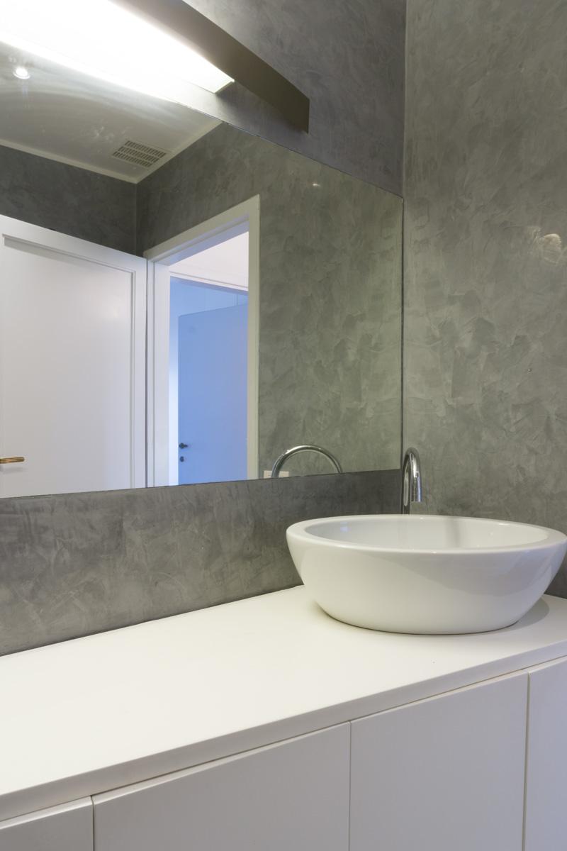 Casa C2- Dettaglio del mobile su misura con lavabo ovale appoggiato sul piano, pareti con finitura a stucco veneziano sui toni del grigio - Tommaso Vecci