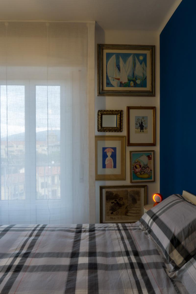 Casa C2- Camera da letto con parete di colore blu, testata da letto in legno e tenda a pacchetto - Tommaso Vecci
