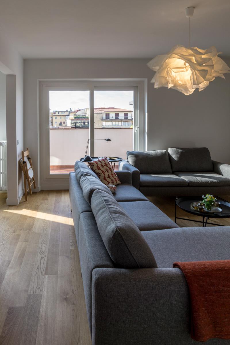 Casa AJ - Zona soggiorno con pavimento in legno, divani di colore grigio, infissi ad ante scorrevoli e lampada in policarbonato - Tommaso Vecci