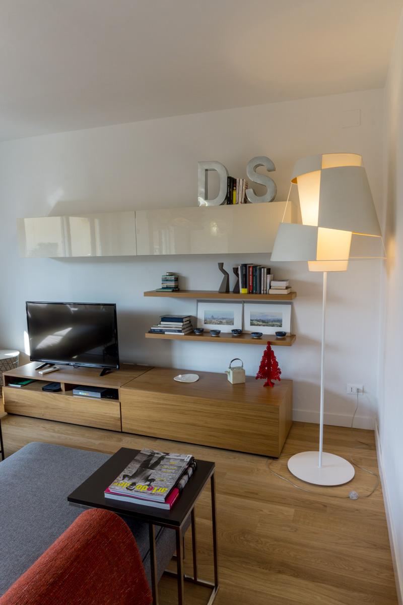 Casa AJ - Dettaglio della zona tv con mobili in legno, lampada a terra e tavolo in acciaio e legno - Tommaso Vecci