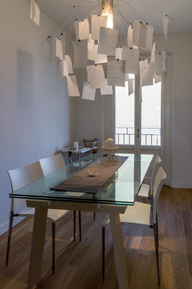 Casa AJ - Vista della zona pranzo con pavimento in legno, portafinestra in legno e tavolo in vetro con sedie in acciaio e ABS - Tommaso Vecci