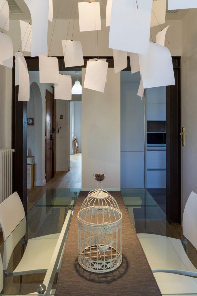 Casa AJ - Dettaglio del tavolo in vetro con sedie in acciaio e ABS della zona pranzo e vista sulla zona cottura - Tommaso Vecci
