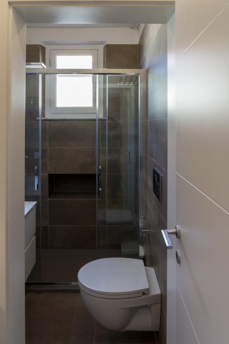 Casa AJ - Dettaglio del bagno, con pavimento e rivestimento in gres con tonalità caffè - Tommaso Vecci