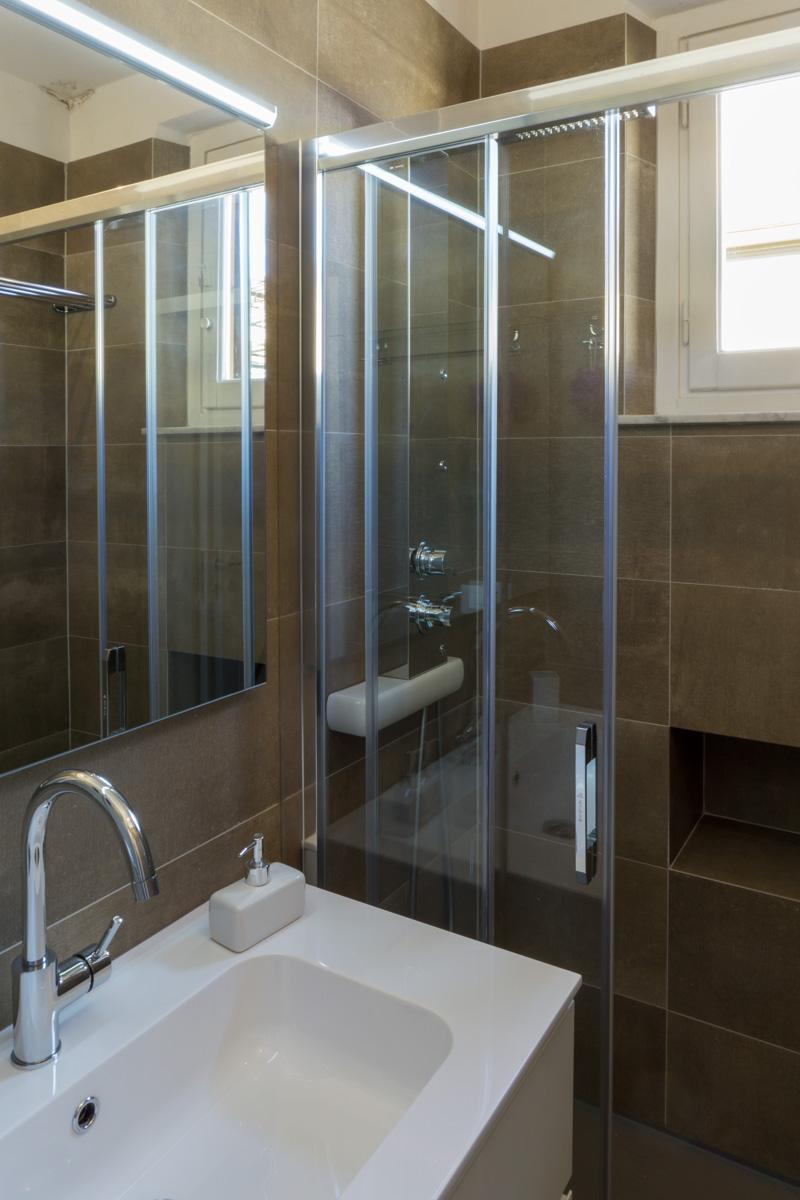 Casa AJ - Dettaglio del lavabo e della doccia, con porta scorrevole in cristallo e colonna idromassaggio - Tommaso Vecci