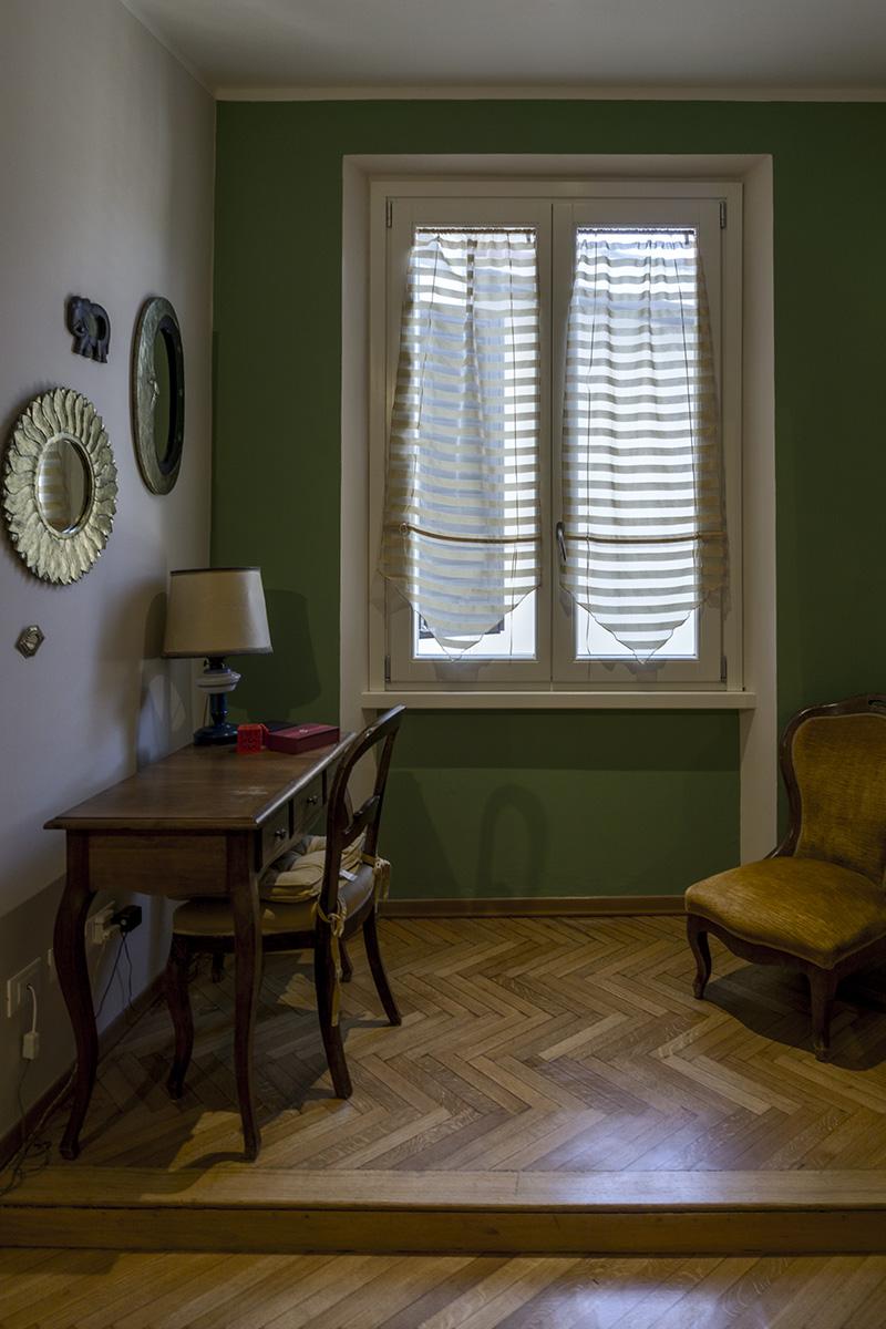 Casa E - Dettaglio camera con parete di colore verde e pavimento in legno - Tommaso Vecci