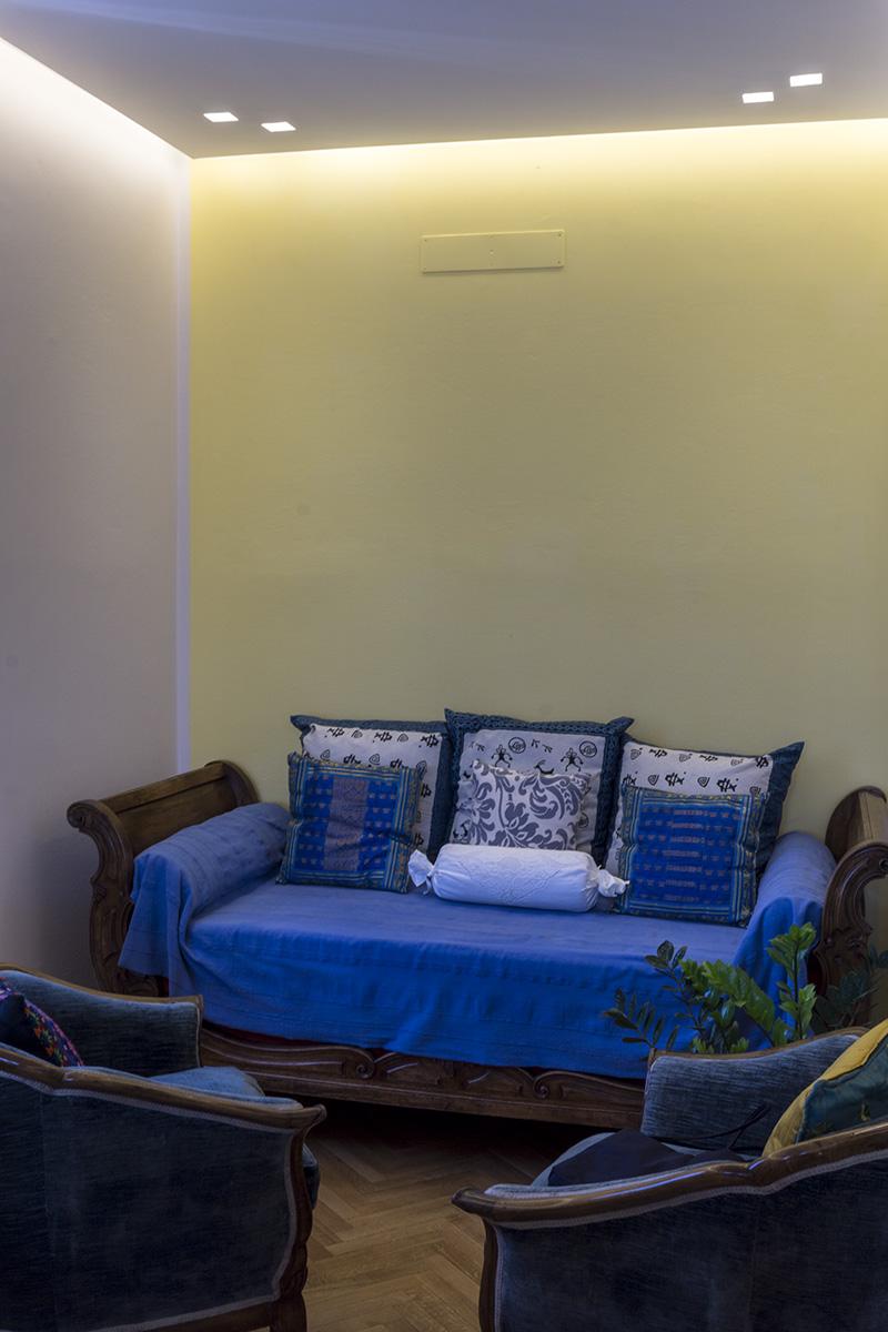 Casa E – Dettaglio zona conversazione con gola di luce a led, controsoffitto con faretti da incasso, pareti di colore giallo e divani con tessuti di colore blu - Tommaso Vecci