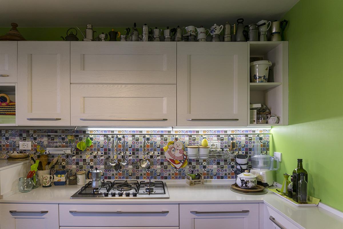 Casa E - Dettaglio cucina con luce sottopensile, piano di lavoro lucido, mobile con ante in legno, rivestimento a parete con icone pop - Tommaso Vecci