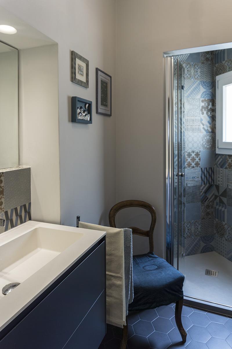 Casa E - Dettaglio del bagno con pareti intonacate, pavimento con mattonelle esagonali e doccia in nicchia con rivestimento decorato - Tommaso Vecci