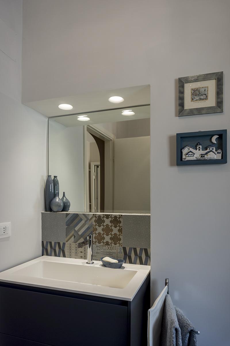 Casa E - Dettaglio del lavabo con specchio in nicchia, veletta in cartongesso con faretti da incasso e parete con rivestimento decorato - Tommaso Vecci