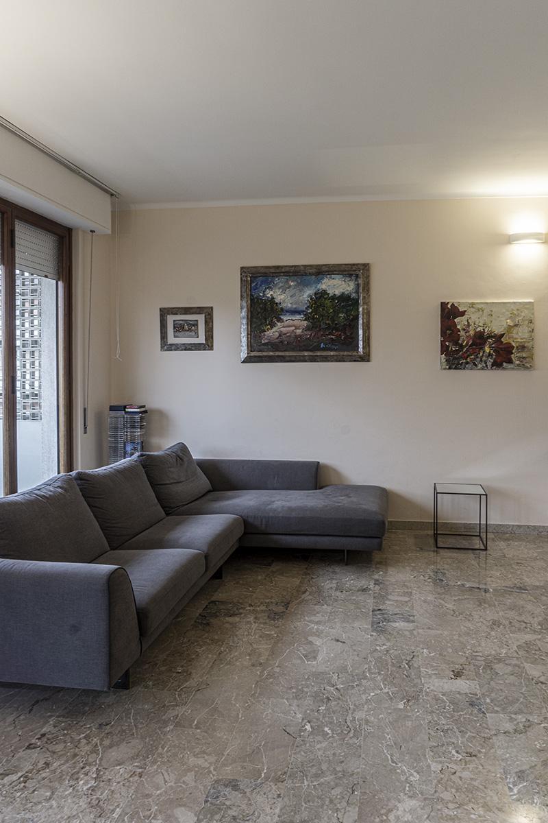 CASA CF - Dettaglio zona conversazione con divano ad L di colore grigio, tavolino in acciaio e vetro - Tommaso Vecci