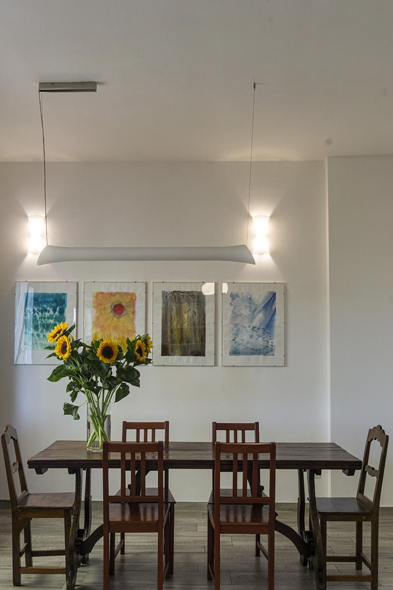CASA MP - Dettaglio zona pranzo con pavimento in ceramica, tavolo e sedie in legno, applique e lampada a sospensione - Tommaso Vecci