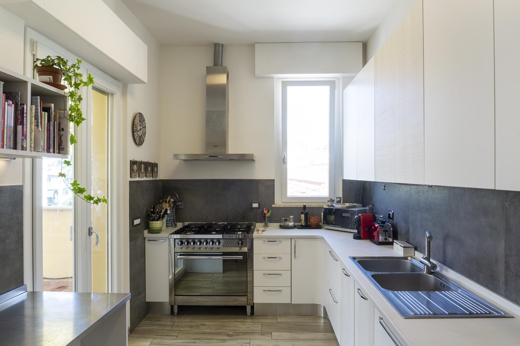CASA MP - Dettaglio cucina con piano di lavoro di colore bianco opaco, lavabo e cappa in acciaio, rivestimento a parete lastre di colore scuro grande formato - Tommaso Vecci