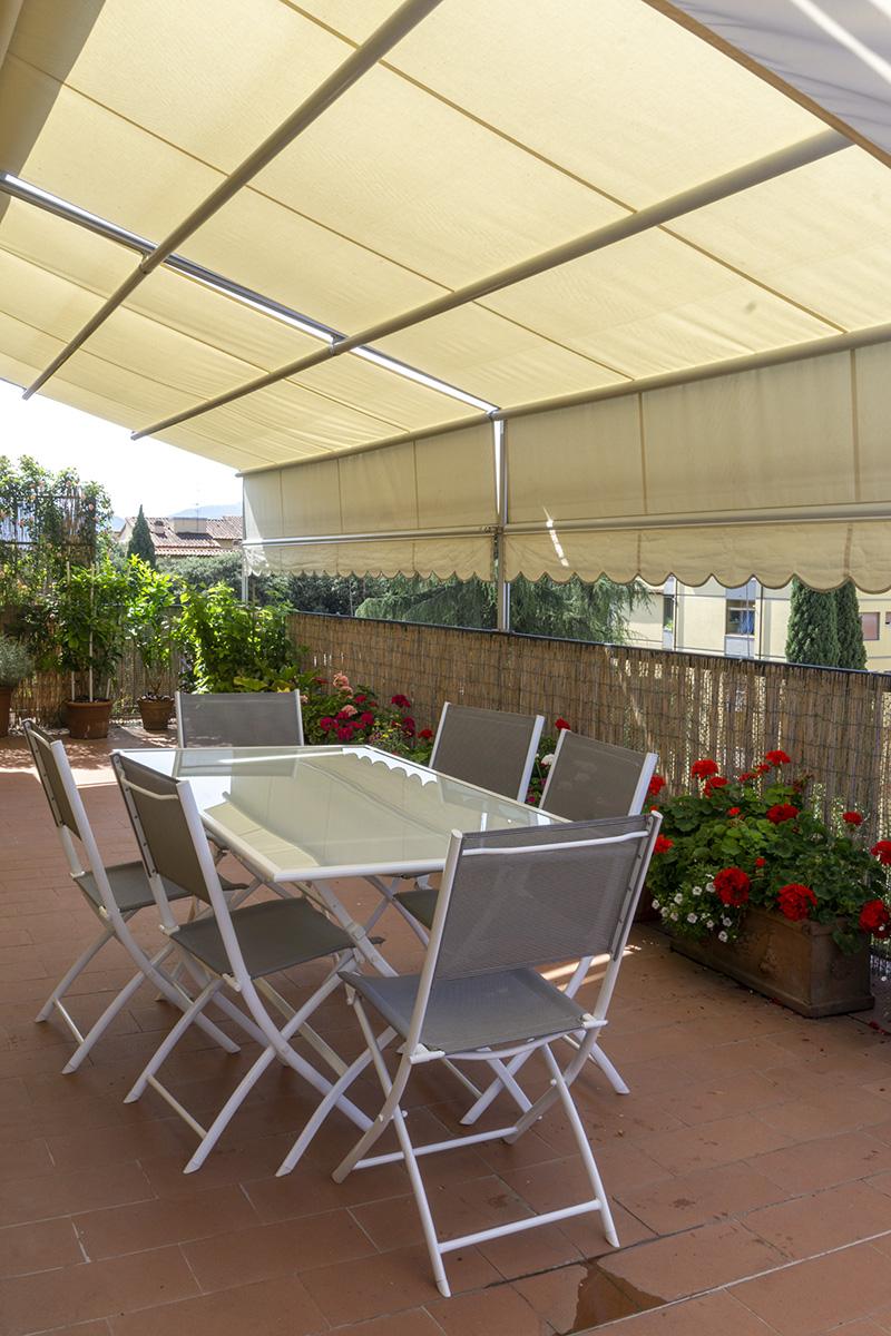 CASA MP - Dettaglio della terrazza con tavolo in acciaio e vetro, sedute in acciaio e tessuto, tenda retrattile - Tommaso Vecci