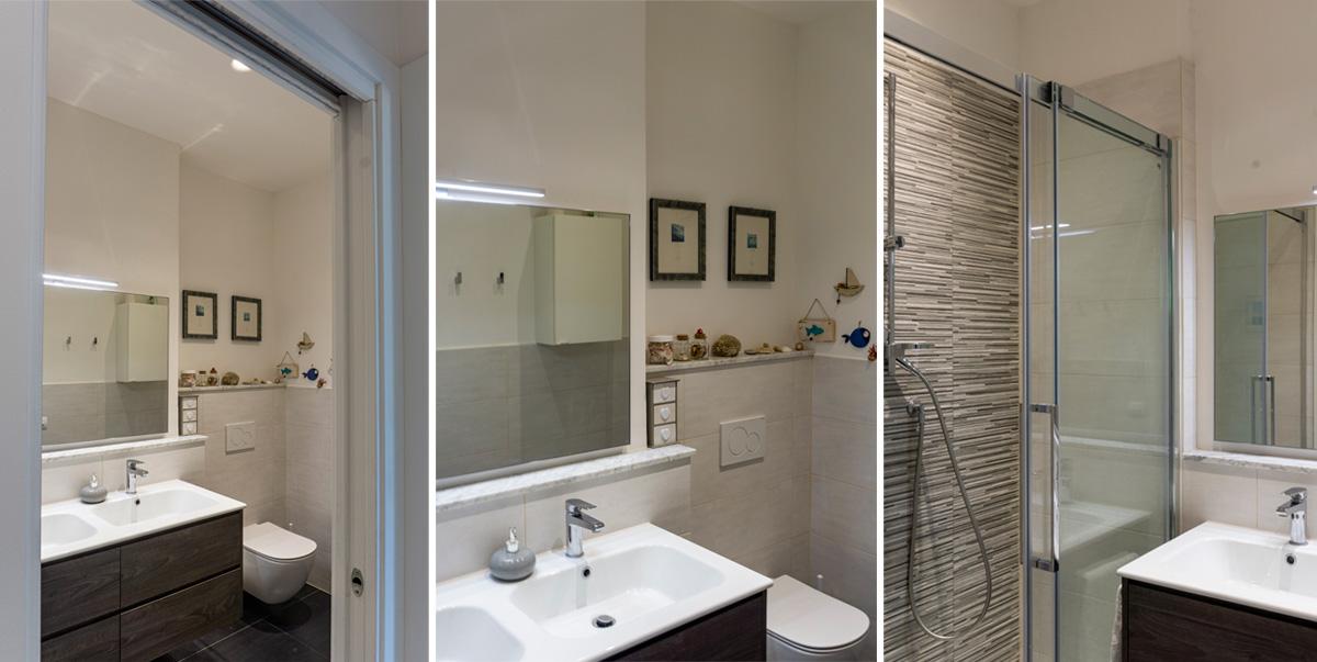 CASA MP - Dettaglio del bagno con box doccia ad anta scorrevole e rivestimento in listelli di mosaico, doppio lavabo e pavimento in ceramica colori scuri - Tommaso Vecci